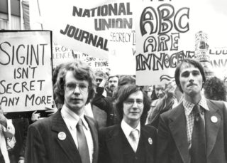 Duncan Campbell and Crispin Aubrey and John Berry at a demonstration, in front of a placard reading